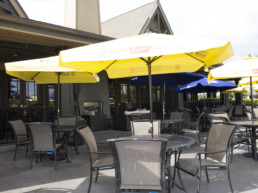 The Gril patio tables with yellow umbrellas at Lewis Estates Golf Course